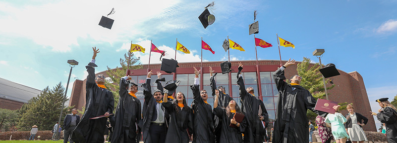 Graduating students throw their mortarboards in the air