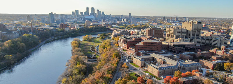 Aerial view of the Minneapolis East Bank campus with the Minneapolis skyline across the Mississippi river